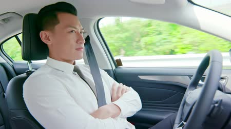 self driving : confident business asian man experience to drive an auto self-driving smart car in highway Stock Footage