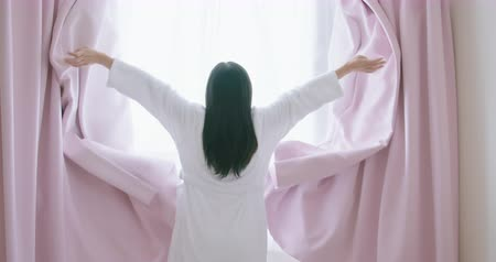 girl in robe : slow motion back view of woman in pajamas stretching arms after wake up in the morning at home