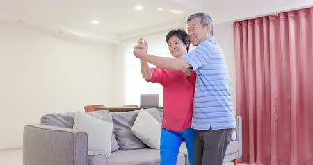 taniec : asian eldely couple dance together happily at home