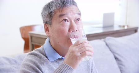 hydratace : asian old man drink water and feel good at home