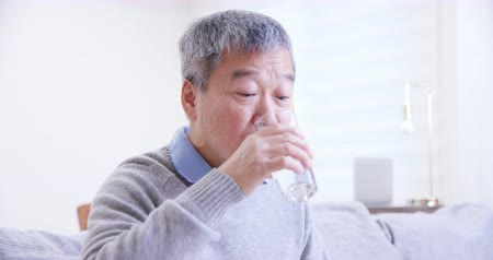 nyel : asian old man eat medicine pills with water and feel better at home