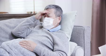 čelo : asian eldely sick man feel headache with mask lying on the sofa at home