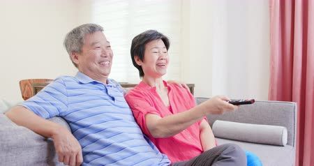aposentar : eldely couple sit on the sofa and watch tv happily with remote control
