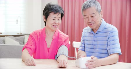 sphygmomanometer : asian elder couple use manometer to test blood pressure happily at home Stock Footage