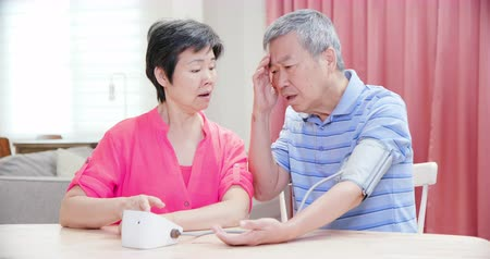 temor : asian elder couple use manometer to test blood pressure and they worry about it