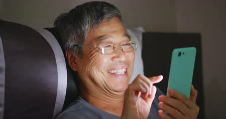 шестидесятые годы : asian elder man use smart phone in the dark