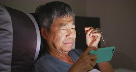 bitkin : asian elder man discomfort to eyes when he use smartphone
