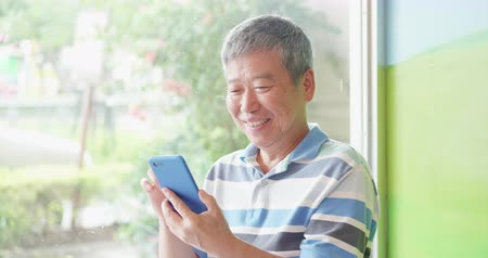 aposentar : asian elder man use smart phone beside windows Stock Footage