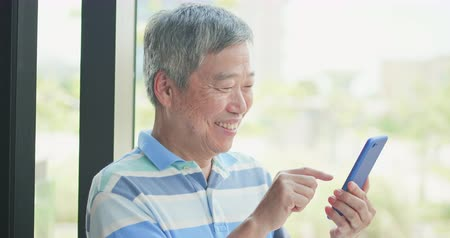 sorridente : asian elder man use smart phone beside windows Vídeos