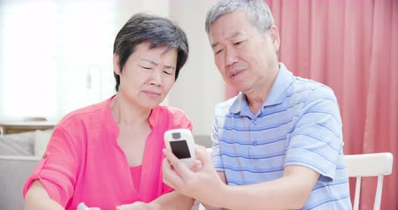 glicose : asian old couple use blood glucose meter and worry about it - Prevention diabetes concept