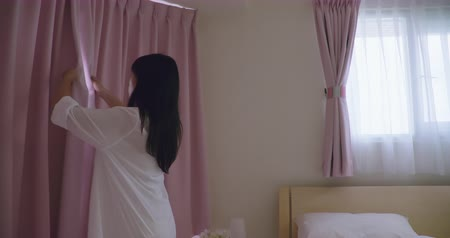 drapes : slow motion of woman opening curtains and stretching arm in the morning at home Stock Footage