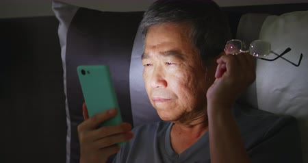 infastidito : asian elder man has farsighted so he takes off glasses when using smartphone Filmati Stock