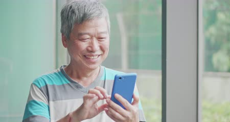 aposentar : asian old man use smart phone beside windows Stock Footage