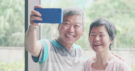 abraço : asian elder couple take selfie happily and look photo on smartphone