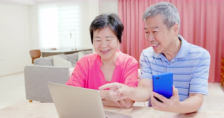 шестидесятые годы : asian elder couple use smart phone and laptop at home