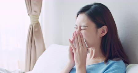 hrdlo : asian woman sick and sneeze with tissue paper in the bedroom