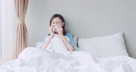 alergia : asian woman sick and sneeze with tissue paper in the bedroom