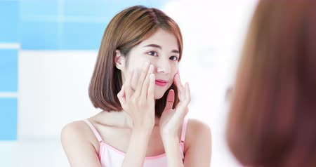 krem : asian beauty woman apply cream on her face and look in mirror