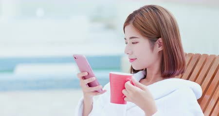 fürdőköpeny : asian beauty woman take selfie when lying on lounge chair to relax with coffee or tea Stock mozgókép