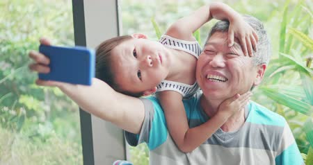 dede : asian elder grandfather take selfie with kid happily