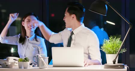 heures supplementaires : asian businessman and businesswoman overtime work and give five for each other in the office