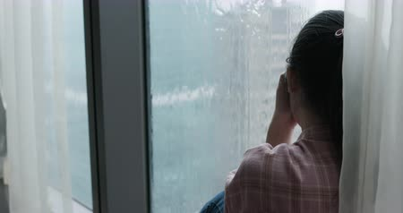 разочарование : asian woman cry and sit by window on a rainy day