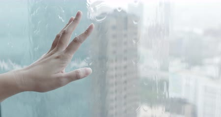 pane : asian woman touch window when raining outside Stock Footage
