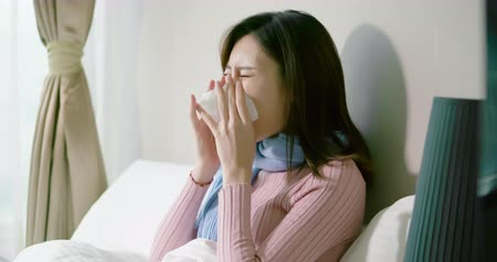 heuschnupfen : slow motion of asian woman sick and sneeze with tissue paper in the bedroom