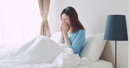 fáradt : asian woman sick and sneeze with tissue paper in the bedroom