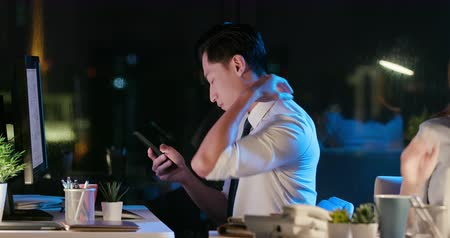 use laptop : asian businessman overtime work and feel shoulder pain in the office when using smartphone