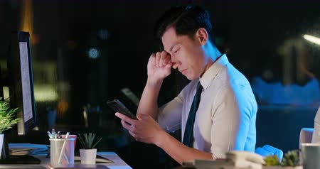 miopia : asian businessman overtime work - he has headache and feels eye pain in the office when using smartphone Filmati Stock