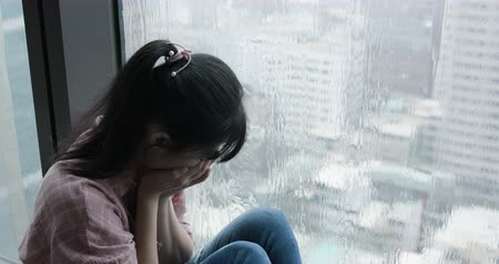 expressivo : asian woman cry and sit by window on a rainy day