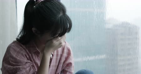 déprimer : asian woman cry and sit by window on a rainy day