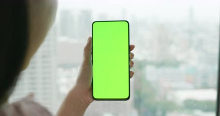 menos : asian woman hold 5g full display phone with green screen