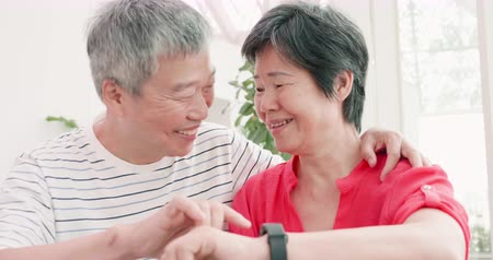 шестидесятые годы : asian elder couple use wearable smart watch happily Стоковые видеозаписи
