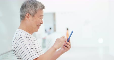использование : asian elder man watch something on smart phone happily