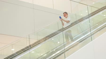 エスカレーター : asian elder man use smart phone in the escalator