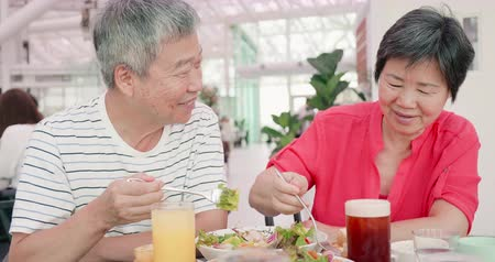 bread pan : asian elder couple is eating in the restaurant and share their food to each other Stock Footage