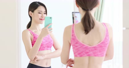 delgado : asian woman take selfie in front of mirror with sport wear happily
