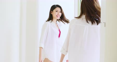 носить : slow motion of asian girl wear white t-shirt and looking in mirror happily Стоковые видеозаписи