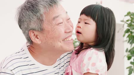 ski : asian granddaughter kiss her old grandfather happily