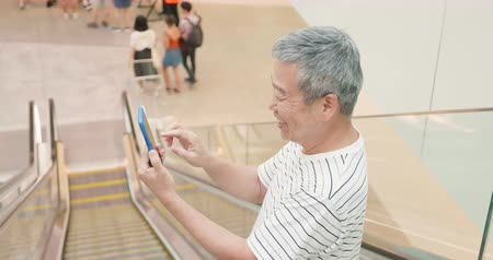 шестидесятые годы : asian elder man use smart phone in the escalator