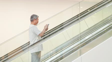 aposentar : asian elder man use smart phone in the escalator