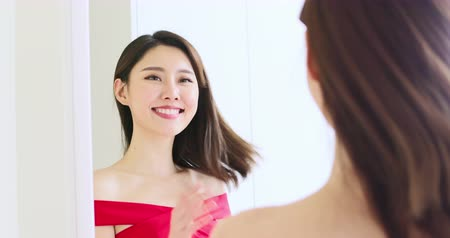 refletir : slow motion of asian girl look mirror and touch her face happily