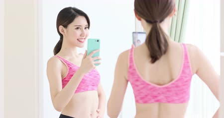 lombo : asian woman take selfie in front of mirror with sport wear happily
