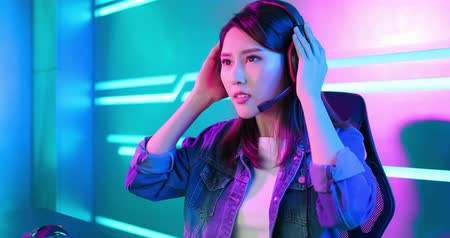 Young asian pro gamer girl wear on headphones and ready to play in online video game Stockvideo