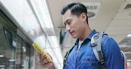 asian young man use 5g smartphone on the mrt station Stock Footage