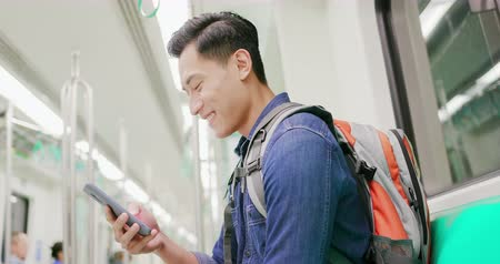 asian young man use 5g smartphone on the mrt or train Stock Footage