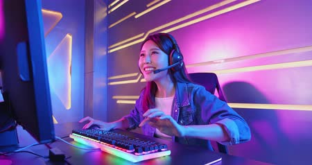 myszka komputerowa : Young Asian Pretty Pro Gamer win in Online Video Game and cheer with hand up