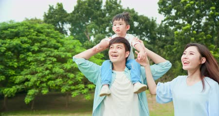 Young parents show the view to kid when let him sit on father shoulder
